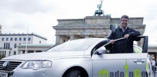 Prof. Dr. Raúl Rojas von der FU Berlin Dahlem mit einem Prototypen eines autonomen VW vor dem Brandenburger Tor in Mitte (Foto: Autonomos-labs.com)